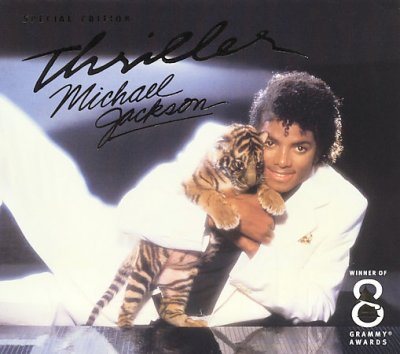 Photo of Michael Jackson half reclining in white sutie, holding a baby tiger with spotlight in the background--CD cover